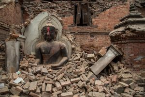 A photograph showing the aftermath Nepal earthquake: an intact statue of Buddha among the rubble and destruction.